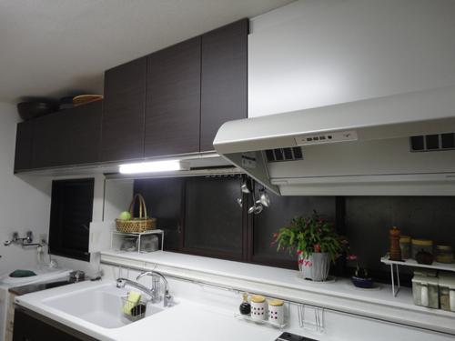トクラスのキッチンです。ダークブラウンの扉が、お部屋によく馴染んでいます。シンクの色はグレーで、落ちついた雰囲気の素敵なキッチンになりました。吊戸棚は壁面いっぱいに付けました。