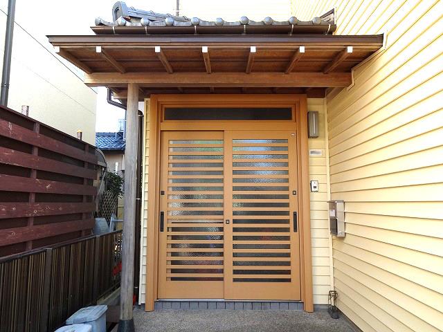 """既存の外壁材の色と、立派な庇(ひさし)に合うような玄関ドアをご提案させて頂きました! """"和""""の雰囲気が強調され、お家の魅力が更にUP! 木目がキレイな新しい玄関ドアは、LIXIL<リシェント(53型 横太格子 欄間B型)>"""