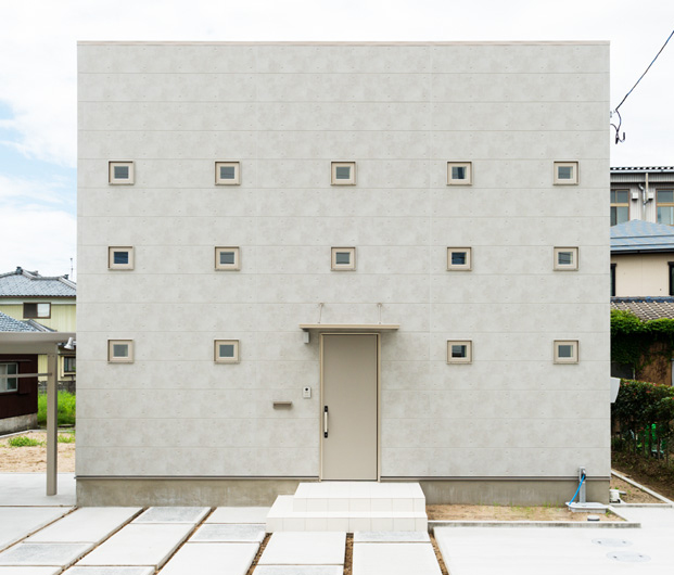 スクエアの小窓が並ぶキューブ型の家。コンクリート調で洗練された印象の外観。